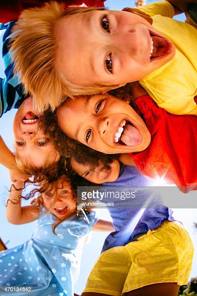Mixed race kids posing above the camera smiling playfully