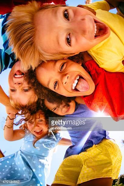 Multiethniques enfants posant souriant à la caméra au-dessus de la porte