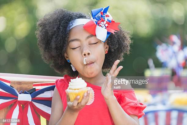 ミックスレース小さな女の子がカップケーキでの 7 月 4 日の
