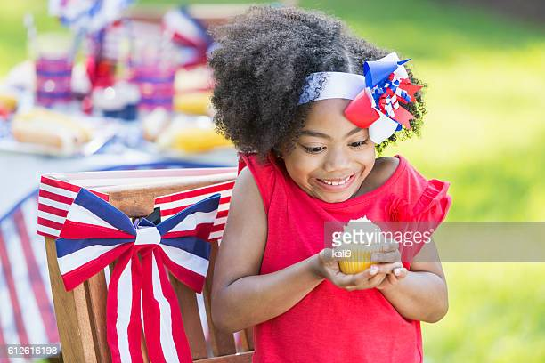 Mixed race little girl having cupcake on 4th of July