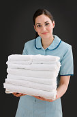 Mixed race maid holding stack of towels