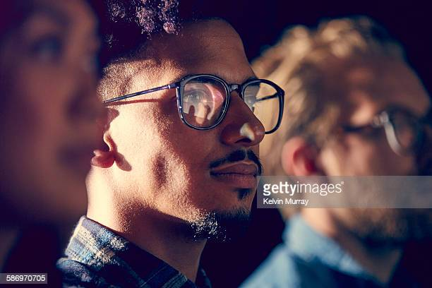 A mixed race male employee watches presentation