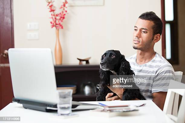 Mixed Race Male on Laptop at home with Dog.