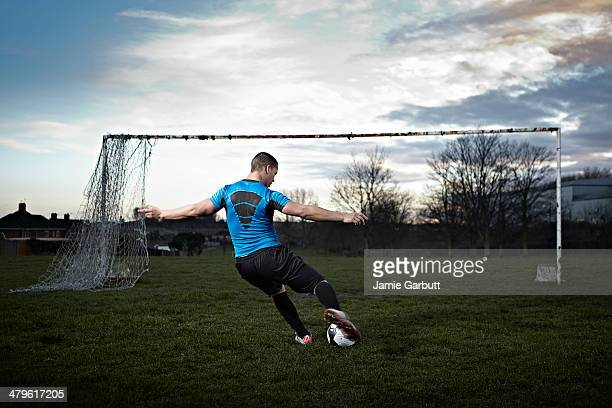 Mixed race male taking a penalty kick