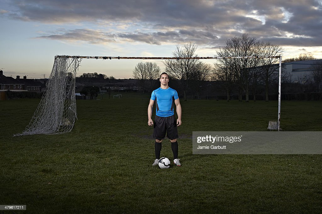Mixed race male with a football at his feet : Stock Photo