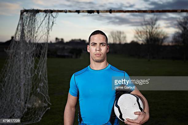 Mixed race male with football under arm