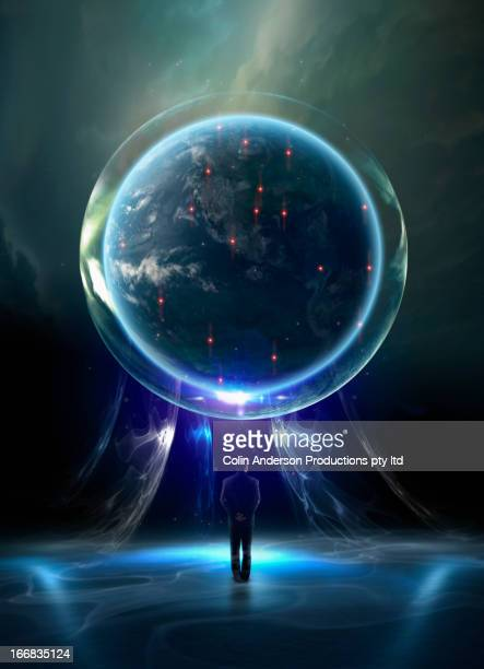 Mixed race man admiring glowing globe