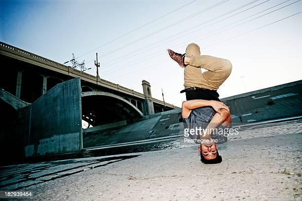 Mixed race man break dancing under overpass