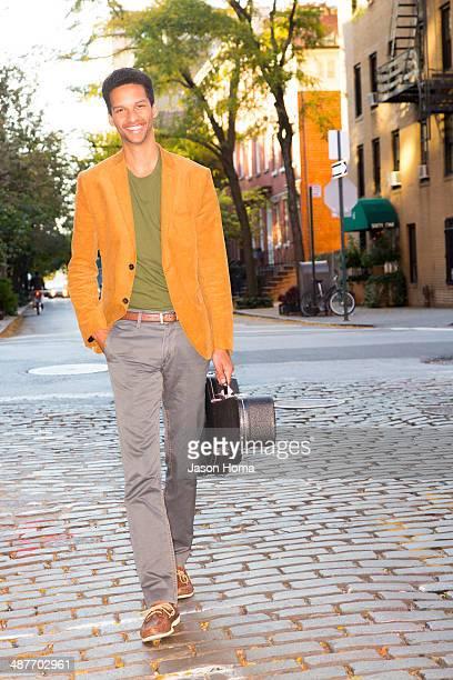 Mixed race man carrying guitar on city street