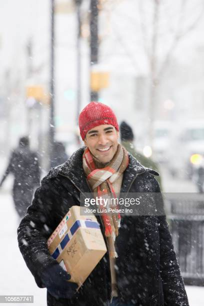 Mixed race man carrying package in snow