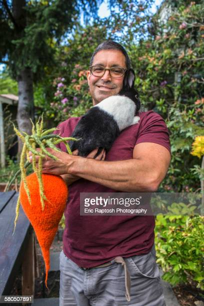 Mixed race man carrying rabbit and knitted carrot