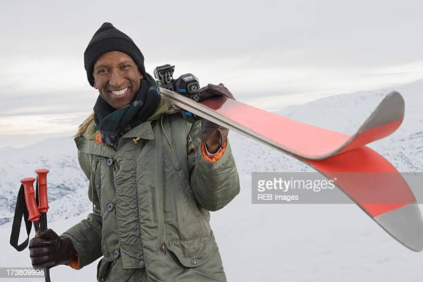 Mixed race man carrying skis on snowy slope