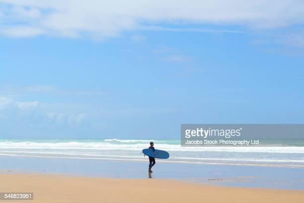 Mixed race man carrying surfboard on beach