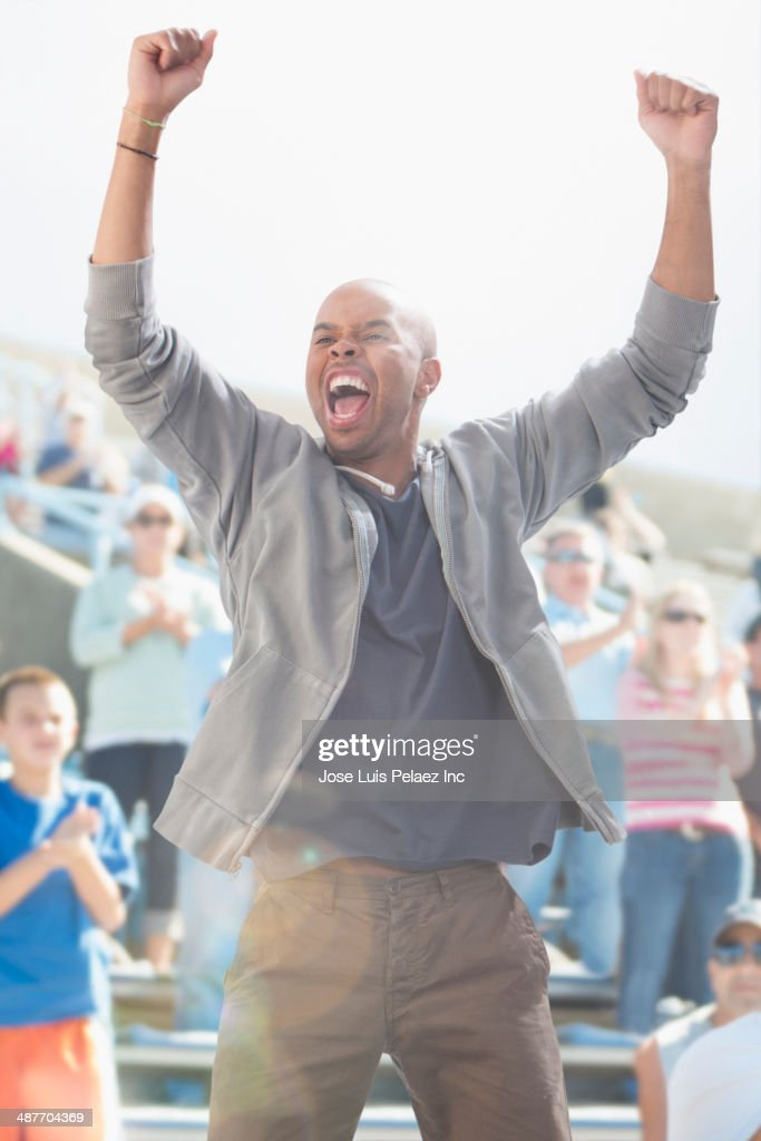 Mixed race man cheering at sporting event : Stockfoto