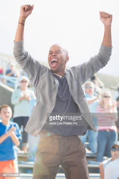 Mixed race man cheering at sporting event