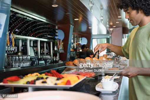 Mixed race man choosing food from breakfast buffet