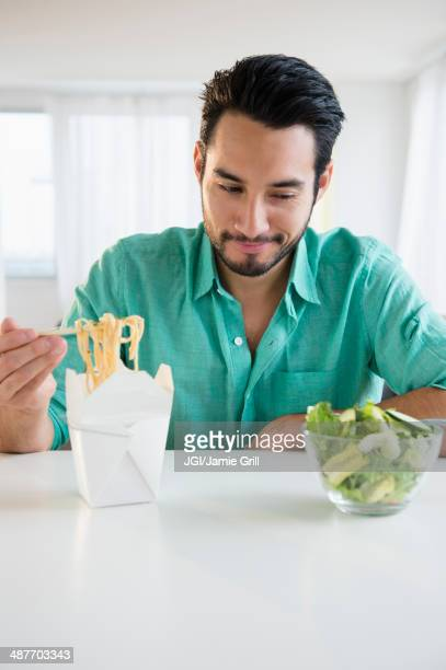 Mixed race man choosing take out or salad