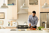 Mixed race man cooking in kitchen