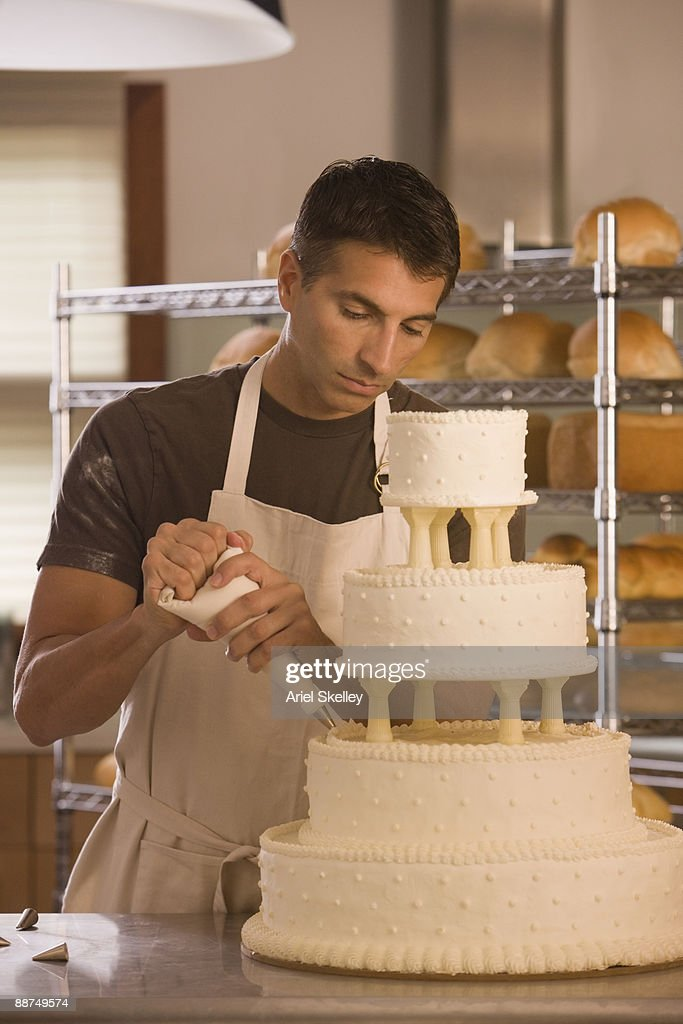 Mixed race man decorating wedding cake : Stock Photo