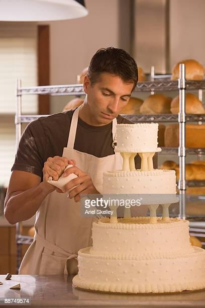 Mixed race man decorating wedding cake