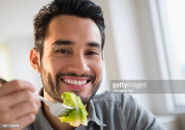 Mixed race man eating salad