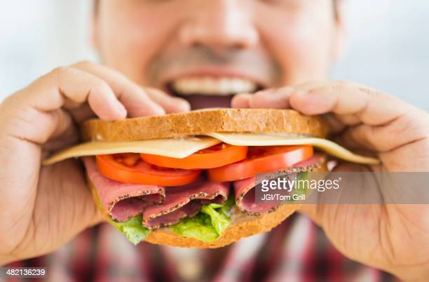 Mixed race man eating sandwich
