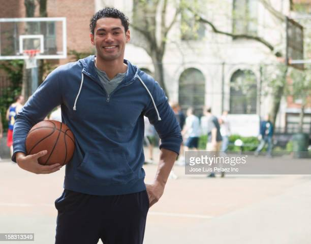 Mixed race man holding basketball on basketball court