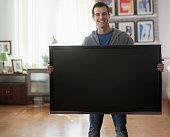 Mixed race man holding big screen television