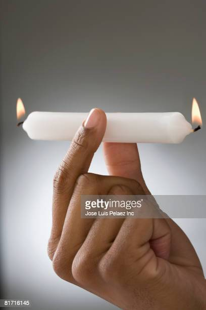 Mixed Race man holding candle burning on both ends