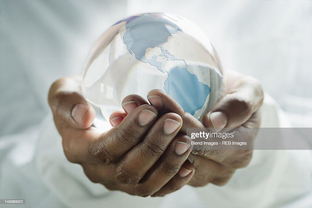 Mixed race man holding glass globe : Stock Photo