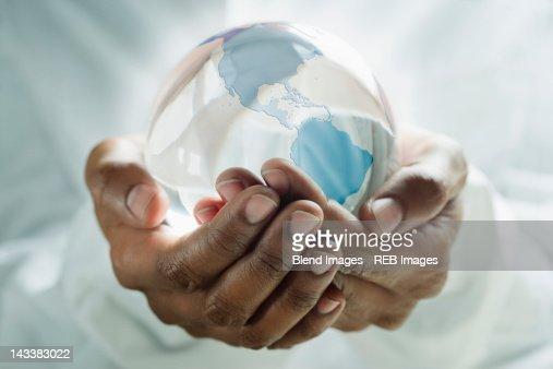 Mixed race man holding glass globe