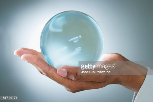 Mixed Race man holding glass orb : Stock Photo