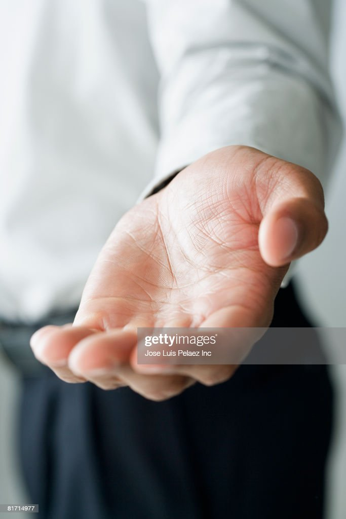 Mixed Race man holding out hand : Stock Photo