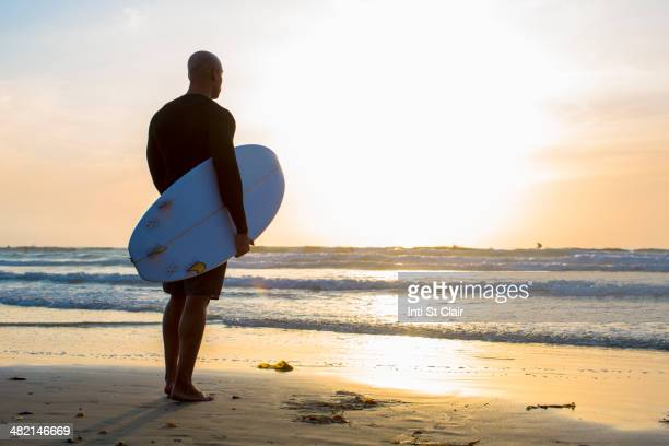 Mixed race man holding surfboard on beach