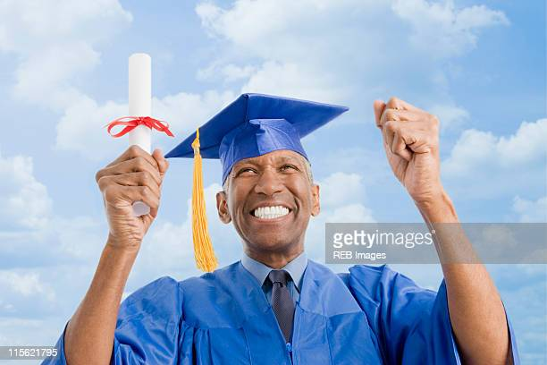 Mixed race man in graduation cap and gown holding diploma