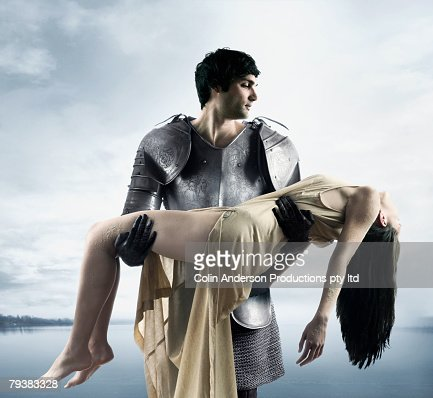 Mixed Race man in suit of armor carrying woman