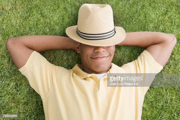Mixed Race man laying in grass
