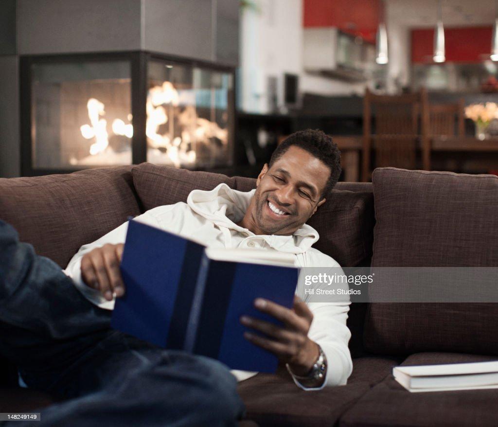 Mixed race man laying on sofa reading book : Stock Photo