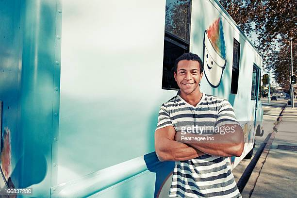 Mixed race man leaning on ice cream truck