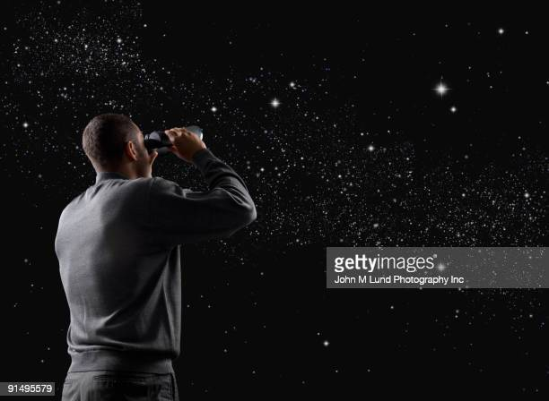 Mixed race man looking at stars in night sky