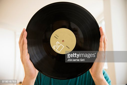 Mixed race man obscuring face with vinyl record