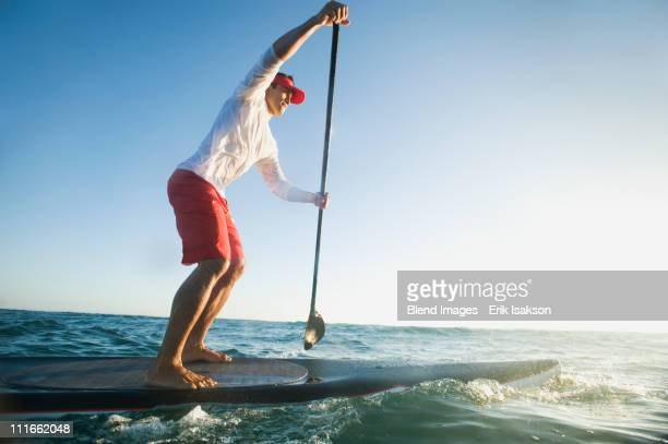 Mixed race man paddling on surfboard
