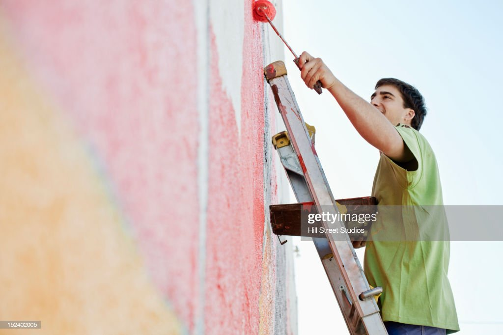 Mixed race man painting wall