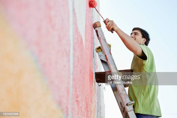 Mixed race man painting wall