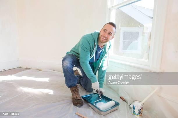 Mixed race man painting walls of home