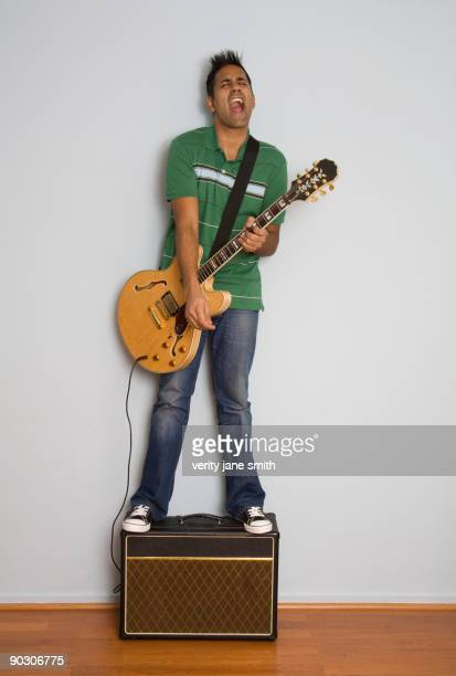 Mixed race man playing electric guitar