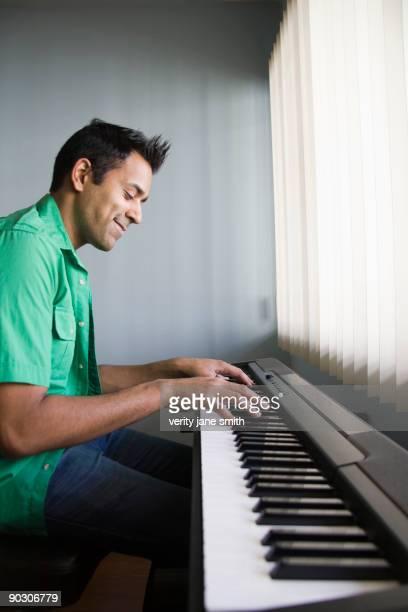 Mixed race man playing electric keyboard