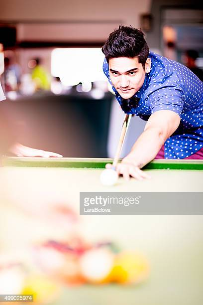 Mixed race man playing pool game in pub