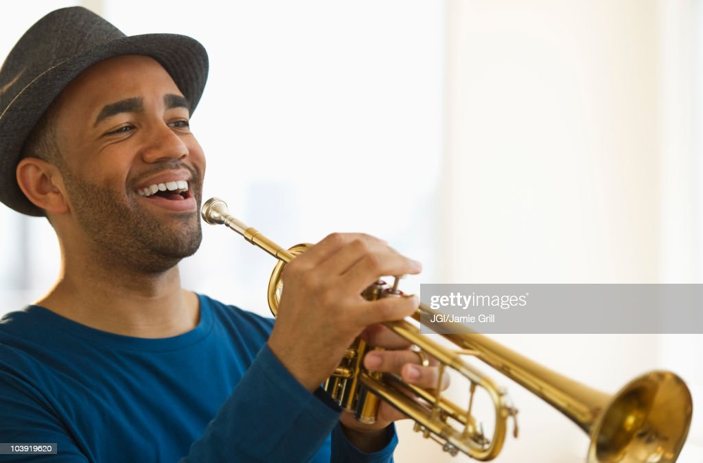 Mixed race man playing trumpet