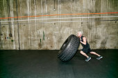 Mixed race man pushing large tire in gym